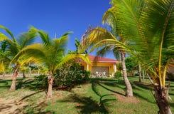 Vista piacevole della casa del bungalow della località di soggiorno che sta nel giardino tropicale contro il fondo del cielo blu Fotografia Stock