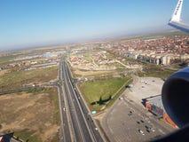 Vista piana aerea di piccola rotonda della strada principale, costruzioni urbane, motore dell'ala, volo di Ryanair sopra la città immagini stock