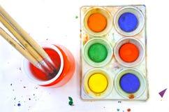 Vista piana di disposizione dei colori di acqua e del pennello su un backgr bianco Immagine Stock
