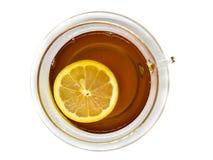 Vista piana di tè in tazza trasparente e di vetro con la fetta di galleggiamento del limone su fondo bianco fotografia stock