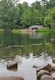Vista pintoresca de un puente viejo en un lago en el parque Foto de archivo