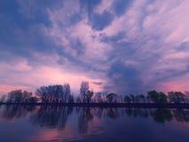 Vista pintoresca del río con las reflexiones de los árboles del riverbank lejano Escena dramática de la tarde debajo de las nubes fotografía de archivo