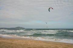 Vista pitoresca da costa com os surfistas do papagaio em ondas Imagens de Stock Royalty Free