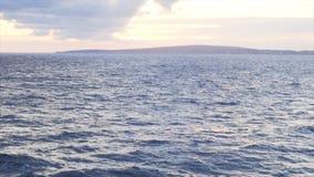 Vista pitoresca da superf?cie da ?gua azul contra o c?u nebuloso do por do sol e da costa de mar no fundo estoque stunning fotografia de stock royalty free