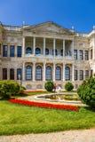 A vista pitoresca de uma das construções do palácio e do parque de Dolmabahce com uma fonte Imagem de Stock