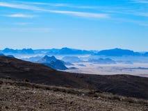 Vista pitoresca dos montes marrons rochosos contra o céu azul brilhante no sul de Jordânia fotos de stock
