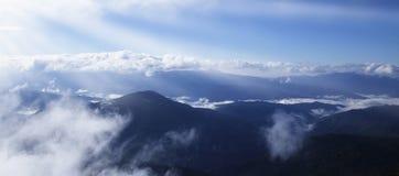 Vista pittoresca delle montagne che emettono luce nell'ambito di luce solare Fotografia Stock