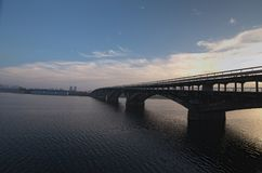 Vista pittoresca sopra il ponte del sottopassaggio della metropolitana sopra il fiume di Dnipro in Kyiv, Ucraina Alba alla mattin Fotografie Stock Libere da Diritti