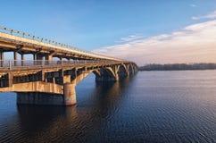 Vista pittoresca sopra il ponte del sottopassaggio della metropolitana sopra il fiume di Dnipro in Kyiv, Ucraina Alba alla mattin Immagini Stock Libere da Diritti