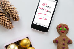 Vista plana del teléfono móvil entre la decoración de la Feliz Año Nuevo Imagen de archivo libre de regalías
