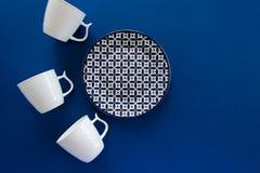 Vista posta piana sopraelevata delle tazze pulite del piatto e di caffè macchiato delle stoviglie su fondo blu scuro fotografie stock