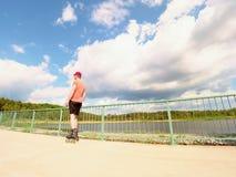 Vista posterior al patinador en línea en camiseta roja y pantalones negros que patina en el puente Patinaje en línea al aire libr Foto de archivo