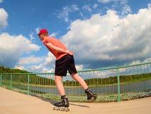 Vista posterior al patinador en línea en camiseta roja y pantalones negros que patina en el puente Patinaje en línea al aire libr Fotografía de archivo libre de regalías