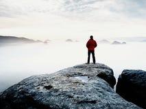 Vista posterior al soporte del viajero solamente en el acantilado con las piernas del bramido de la niebla, sol en cielo nublado imagenes de archivo