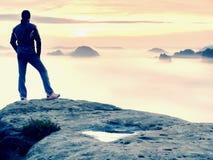 Vista posterior al soporte del viajero solamente en el acantilado con las piernas del bramido de la niebla, sol en cielo nublado imagen de archivo libre de regalías
