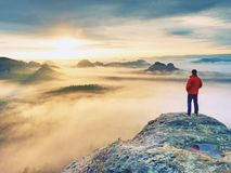 Vista posterior al soporte del viajero solamente en el acantilado con las piernas del bramido de la niebla, sol en cielo nublado foto de archivo