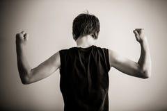 Vista posterior blanco y negro del bíceps que dobla adolescente Imagenes de archivo