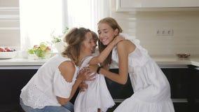 Vista posterior cercana para arriba de una muchacha con el pelo ligero que corre en el cuarto en los brazos de su madre y hermana almacen de video