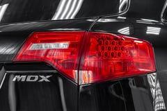 Vista posterior de Acura usado MDX color del negro de 2008 años con las luces traseras rojas que se colocan en la caja de servici foto de archivo libre de regalías