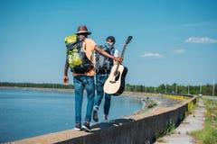 vista posterior de amigos con las mochilas y caminar de la guitarra Imágenes de archivo libres de regalías