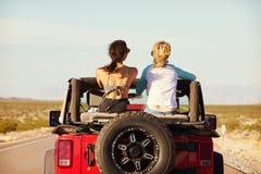 Vista posterior de amigos en el viaje por carretera que conduce en coche convertible Imagen de archivo