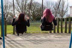 Vista posterior de dos adolescentes que balancean en oscilaciones Fotografía de archivo