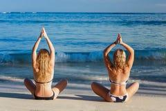 Vista posterior de dos muchachas que hacen yoga en la playa tropical Imagenes de archivo