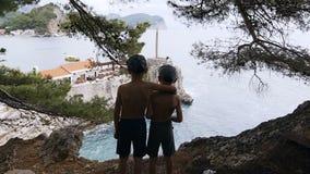 Vista posterior de dos muchachos que se colocan en alta roca y que admiran el mar Día de fiesta de la playa La silueta de la situ almacen de video