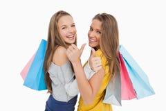 Vista posterior de dos mujeres jovenes el pulgar-para arriba con los bolsos de compras Fotografía de archivo