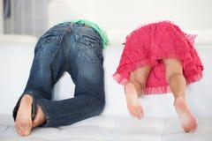 Vista posterior de dos niños que juegan en el sofá fotografía de archivo libre de regalías