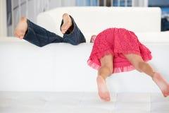 Vista posterior de dos niños que juegan en el sofá fotos de archivo