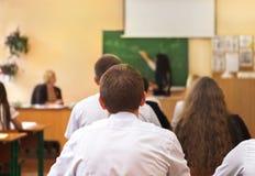 Vista posterior de estudiantes en la sala de clase Fotos de archivo