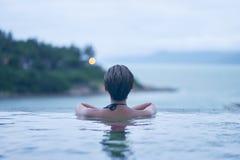 Vista posterior de la belleza asiática que sonríe y que se relaja en piscina en el amanecer foto de archivo