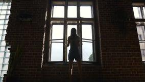 Vista posterior de la chica joven europea que abre una ventana en la calle en día de la mañana del verano La muchacha delgada est metrajes