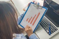 Vista posterior de la empresaria en informes financieros de lectura de la camisa azul foto de archivo libre de regalías