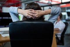 Vista posterior de la empresaria que se relaja en la silla Fotos de archivo