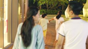 Vista posterior de la familia asiática de 4 que camina en un área de compras en la noche metrajes