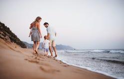 Vista posterior de la familia con dos ni?os del ni?o que caminan en la playa el vacaciones de verano fotos de archivo