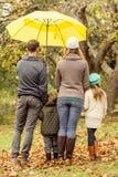 Vista posterior de la familia joven debajo del paraguas Fotografía de archivo