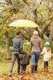 Vista posterior de la familia joven debajo del paraguas Imágenes de archivo libres de regalías