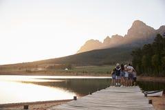 Vista posterior de la familia multi de la generación que defiende en el embarcadero el lago fotografía de archivo