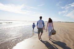 Vista posterior de la familia que camina a lo largo de la playa con la cesta de la comida campestre Foto de archivo libre de regalías