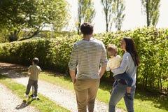 Vista posterior de la familia que va para el paseo en campo del verano fotografía de archivo