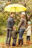 Vista posterior de la familia sonriente joven debajo del paraguas Fotografía de archivo libre de regalías