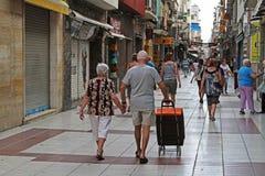 Vista posterior de la gente que camina en una calle peatonal Carrer Esglesia en Calella Foto de archivo