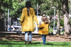 Vista posterior de la madre y de la peque?a hija, vestida en la chaqueta amarilla, caminando y llevando a cabo las manos en el pa imagen de archivo libre de regalías
