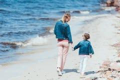 vista posterior de la mamá y de la hija que celebran las manos y caminar fotografía de archivo libre de regalías