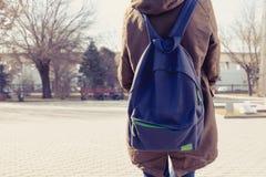Vista posterior de la mochila que cuida de la muchacha del inconformista en ella detrás, copyspace Imagen de archivo libre de regalías