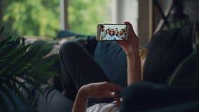 Vista posterior de la morenita que hace la llamada video en línea que sostiene el smartphone que mira la pantalla que habla y que almacen de metraje de vídeo