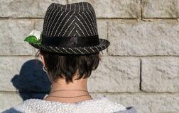 Vista posterior de la muchacha adolescente en el sombrero en fondo de la pared de piedra clos Foto de archivo libre de regalías